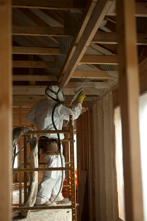 Installer applying spray foam into a home